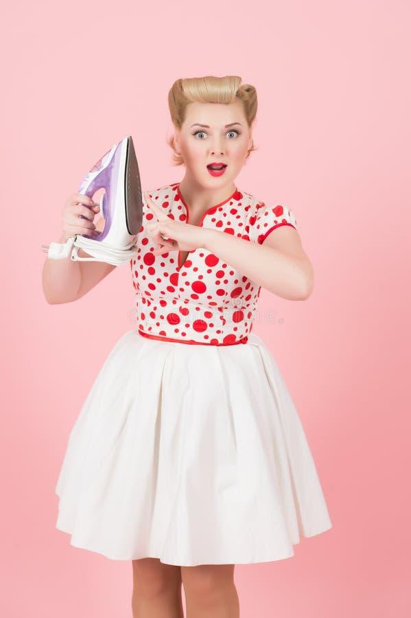 Varmt järn i händer av utvikningsbilden utformade den förvånade blonda flickan arkivfoton