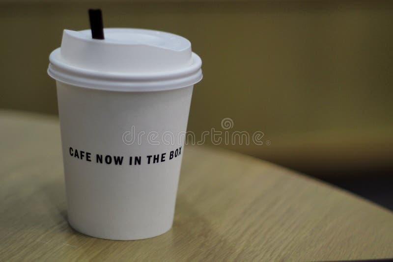Varmt kaffe i pappers- kopp på wood tabellbakgrund fotografering för bildbyråer