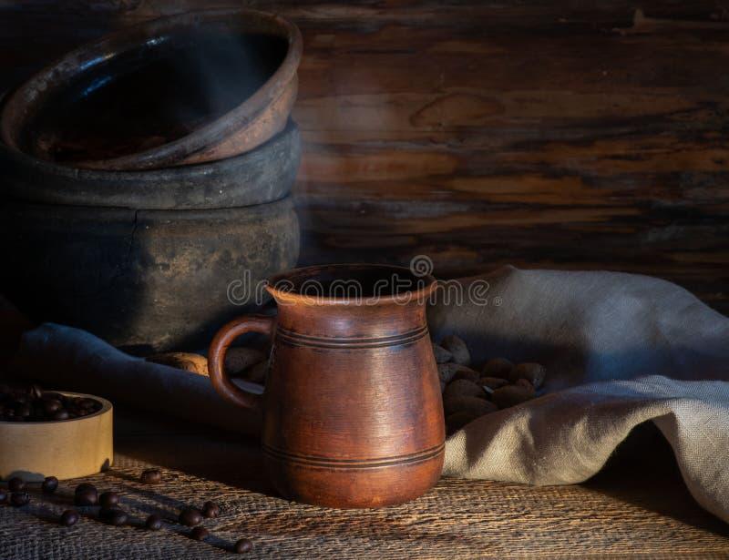 Varmt kaffe i rånar med ånga på ett träbräde mot bakgrunden av gammal keramisk bordsservis Lantlig stil b?nor frukosterar ideal i arkivbilder