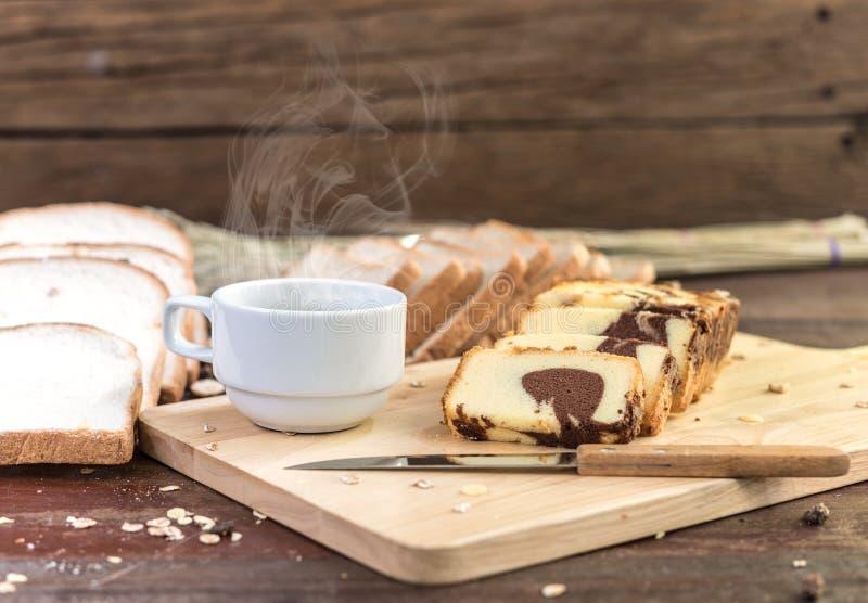 Varmt kaffe med kakan och bröd på trätabellen royaltyfri foto