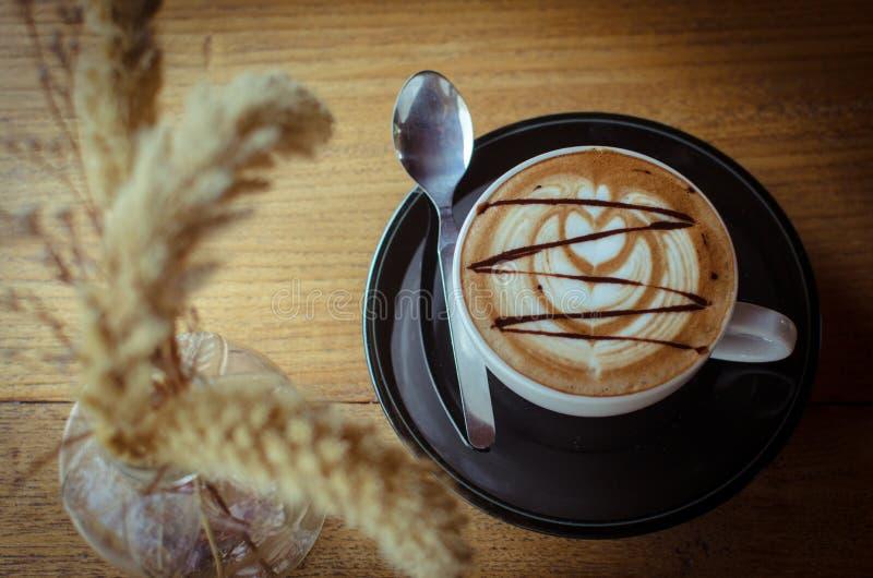 Varmt kaffe med lattekonst är på den wood tabellen arkivfoton