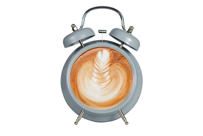 Varmt kaffe med skummigt skum i blå alarmclock royaltyfri bild