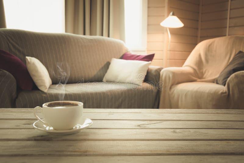 Varmt kaffe på tabletopen i modern vardagsrum i lantlig stil Suddig abstrakt bakgrund för design royaltyfri bild