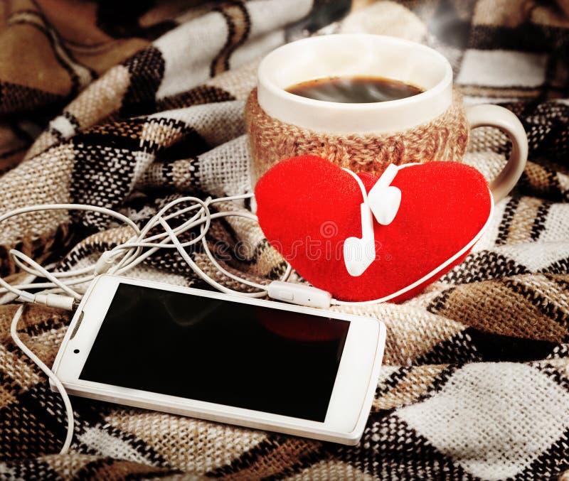 Varmt kaffe, vit mobiltelefon med hörlurar, mjuk röd hjärta royaltyfria bilder