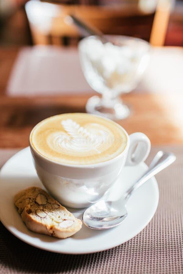 Varmt konstLattekaffe i en kopp med biscotti på trätabell- och coffee shopsuddighetsbakgrund med bokehbild royaltyfri fotografi