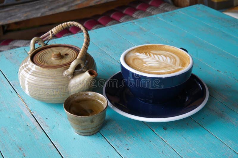 Varmt konstLattekaffe och te i en kopp på den blåa trätabellen royaltyfria bilder
