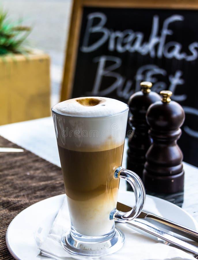 Varmt lattemacchiatokaffe med smakligt skum och kanel arkivbilder