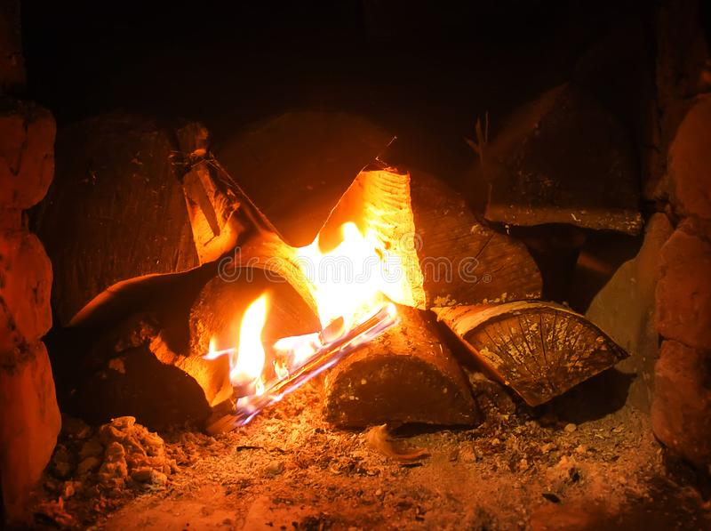 Varmt ljus av en brinnande brand i en spis i gammal rysk ugn Flamma- och vedträbakgrund Detalj av inre arkivfoto
