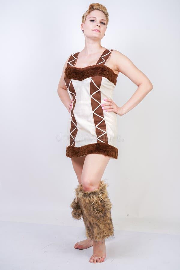 Varmt plus formatkvinna i pälskarnevaldräkt av den primitiva mannen på vit bakgrund i studio en härlig vild flicka i en brun dre arkivfoto