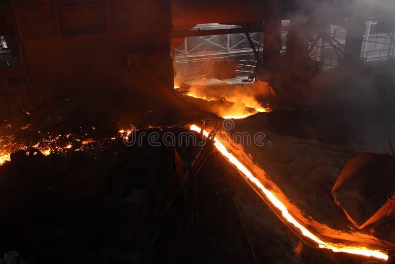 Varmt smält järn som flödar i kanalen i järnfabrik arkivfoto