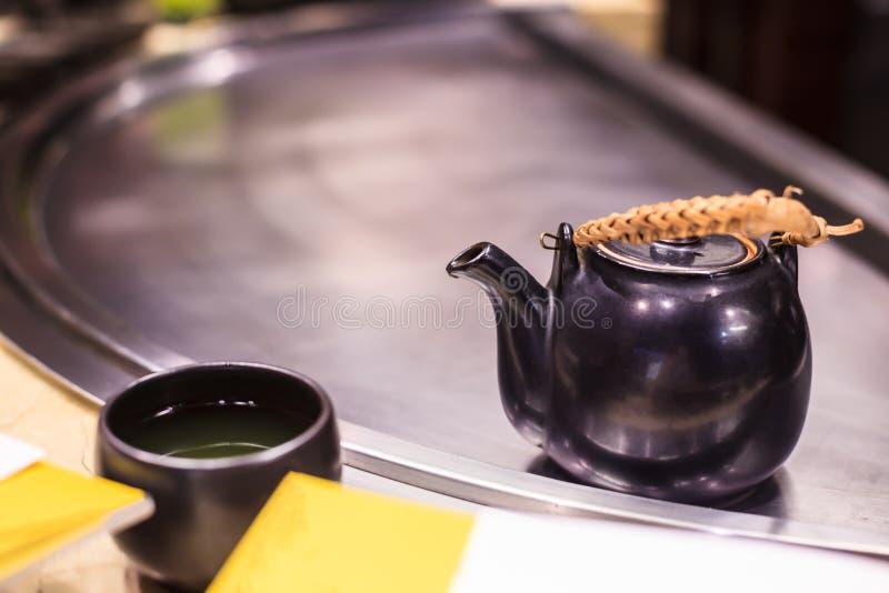 Varmt smakligt växt- Matcha för drink grönt te i svart lergodskopp från värmekokkärlet på metalllaggbakgrund Ha sunt fotografering för bildbyråer
