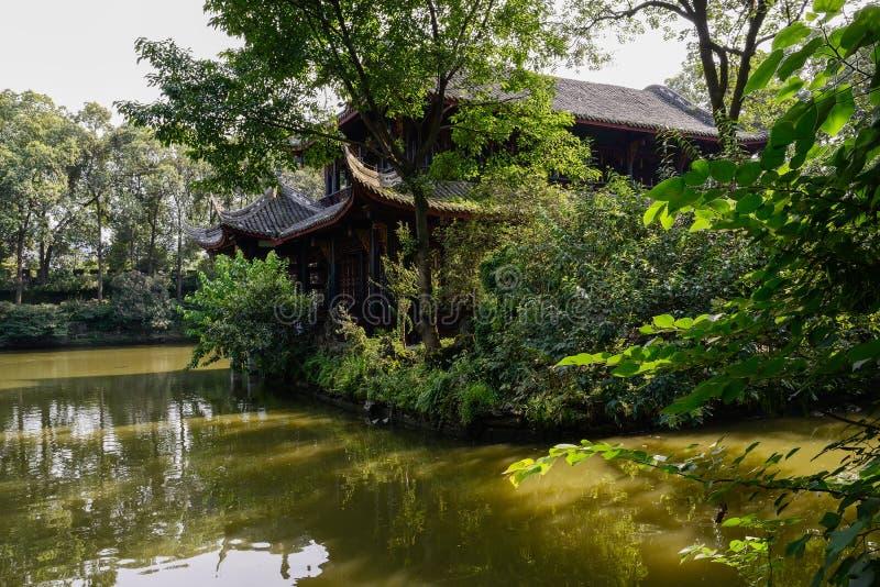 Varmt sommareftermiddagsolsken på åldrig kinesisk byggnad i sjön royaltyfria foton