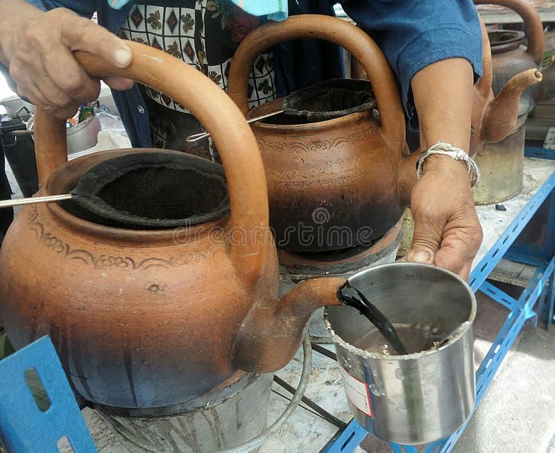Varmt svart kaffe från lerakokkärlet royaltyfria bilder