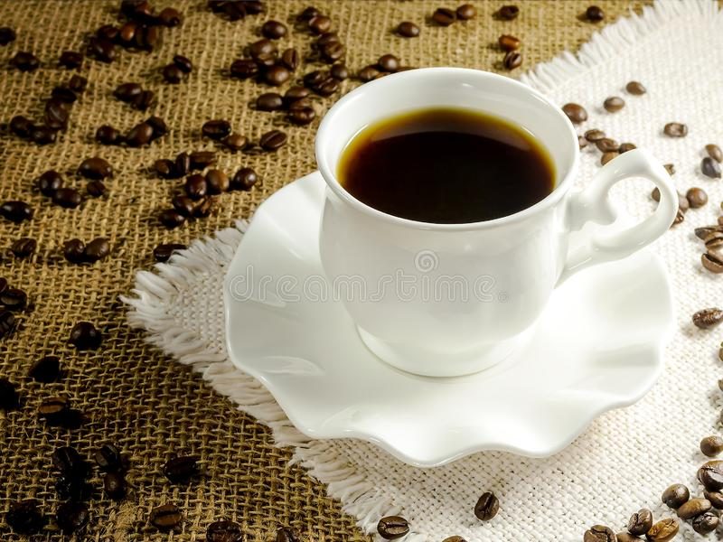 Varmt svart kaffe i en vit elegant kopp på över bakgrund av den beigea tabellservetten med frans- och kaffebönor Varm morgon royaltyfri fotografi