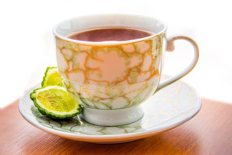 Varmt te med bergamoten på trätabellen i förkylningen royaltyfria bilder