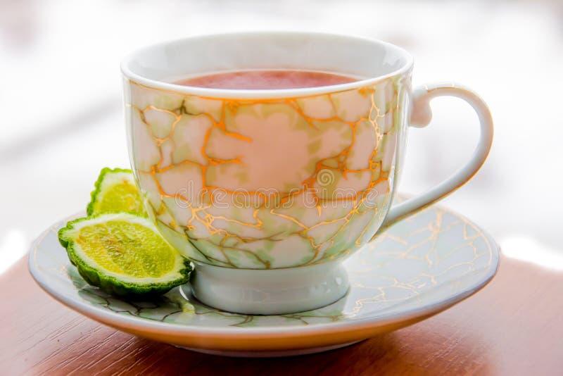 Varmt te med bergamoten på trätabellen i förkylningen arkivbild