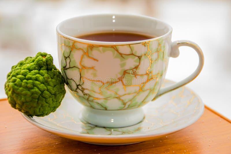 Varmt te med bergamoten på trätabellen i förkylningen royaltyfri fotografi