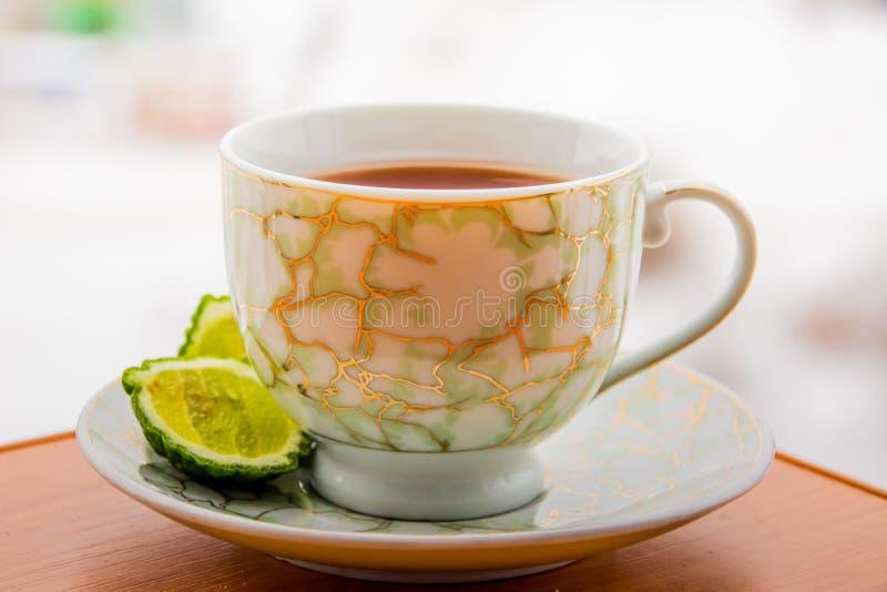 Varmt te med bergamoten på trätabellen i förkylningen arkivfoto