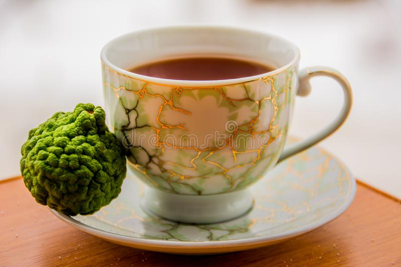 Varmt te med bergamoten på trätabellen i förkylningen royaltyfri foto