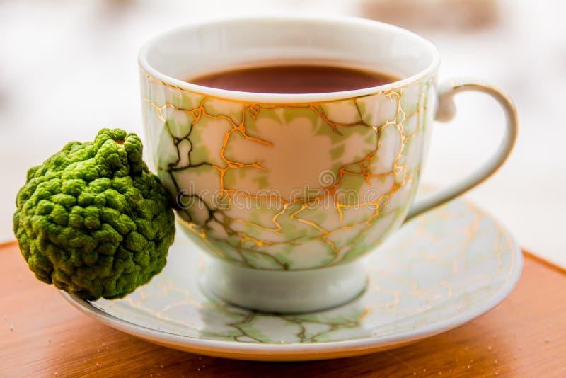 Varmt te med bergamoten på trätabellen i förkylningen arkivfoton