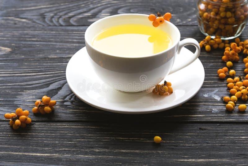 Varmt te med nya havsbuckthornbär royaltyfri fotografi