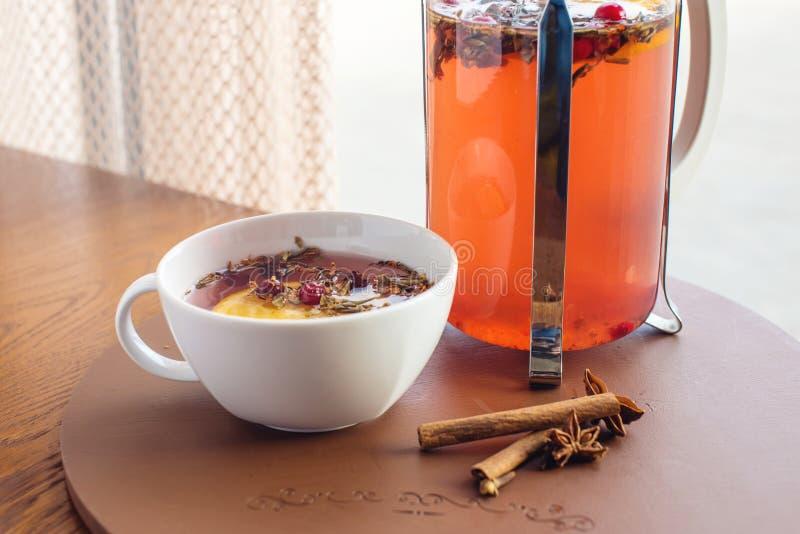 Varmt te med tranbär och örter i en fransk press royaltyfri foto