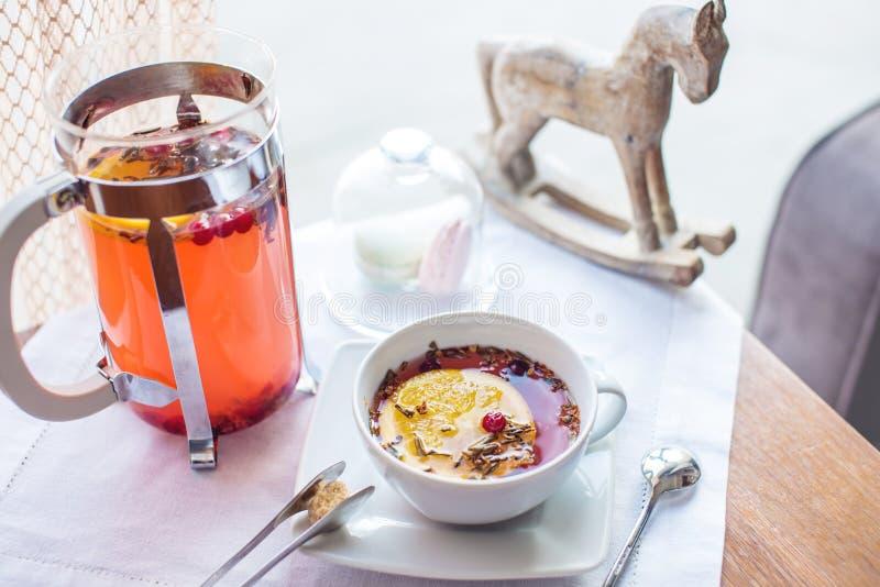 Varmt te med tranbär och örter i en fransk press arkivbild
