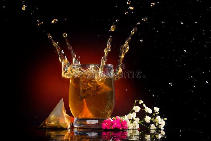 Varmt te som plaskar från exponeringsglaset royaltyfri fotografi