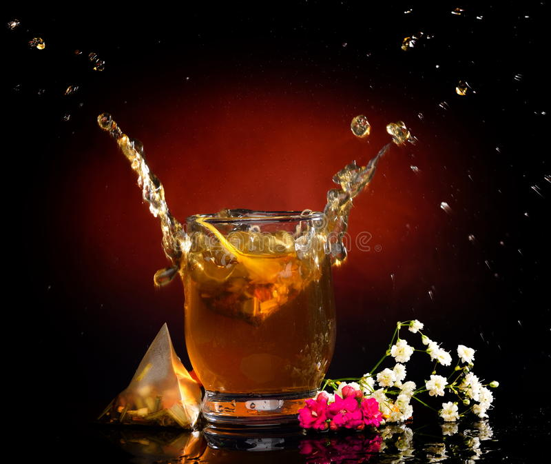 Varmt te som ut plaskar fo exponeringsglaset royaltyfria bilder