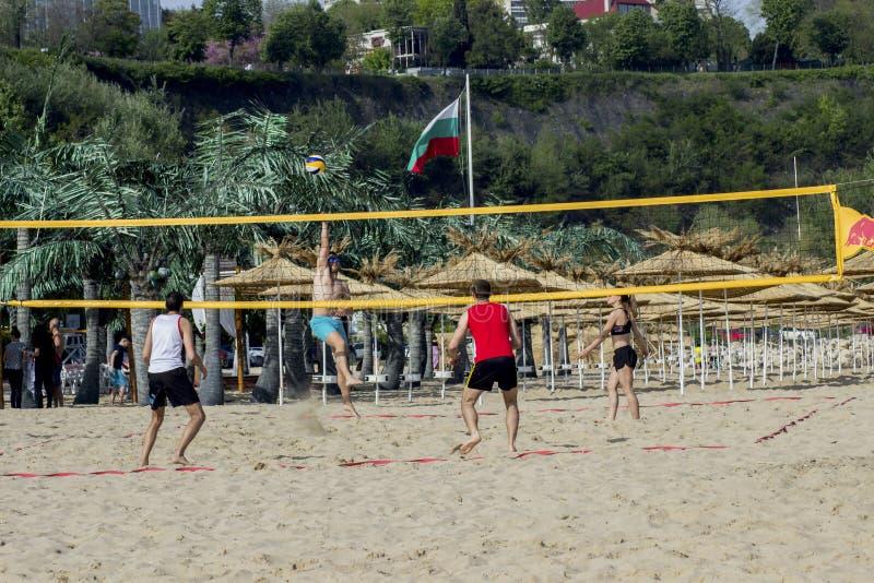 Varna Bulgaria gente del 13 de mayo de 2017 monta las bicicletas en el voleibol del juego de la gente del parque en la playa fotos de archivo libres de regalías