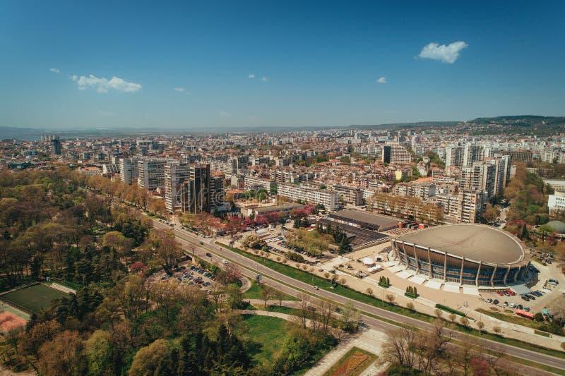 Varna, Bulgaria Il palazzo di cultura e sport ed il mare fanno il giardinaggio Siluetta dell'uomo Cowering di affari immagini stock libere da diritti