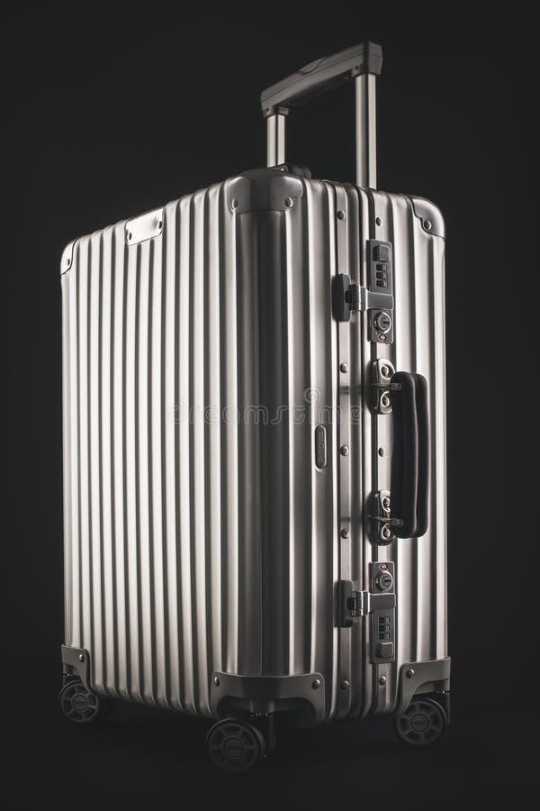 Suitcase or traveling luggage bag isolated on black background. Varna, Bulgaria - May 19 2018 - Rimowa traveling luggage bag or business suitcase studio isolated stock photo