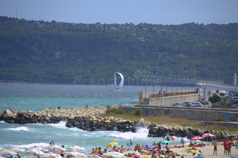 Varna city waterfront view. Vacationing people on red flag summer beach by rough sea,Varna.Bulgaria stock image