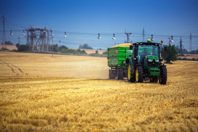 Varna Region, Bulgaria - June 20, 2015: A modern John Deere 6115R tractor with the trailer on a yellow field.The 6115R has. Premium ComfortView cab.Full Frame royalty free stock photo