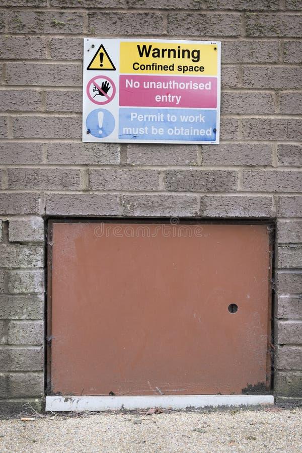 Varnande begränsat utrymmetecken inget obehörigt vård- tillträdestecken och dörr för tillträde för säkerhetskonstruktionsplats fotografering för bildbyråer