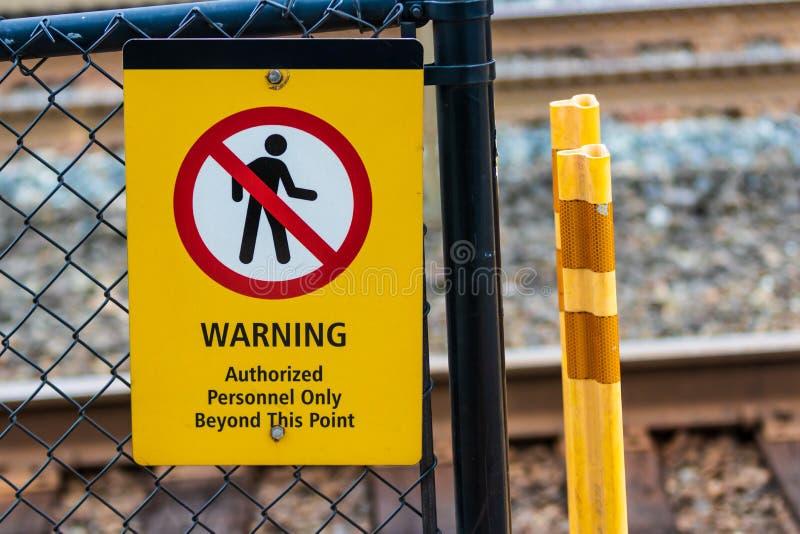 Varnande behöriga personaler undertecknar på ett staket för chain sammanlänkning arkivbilder