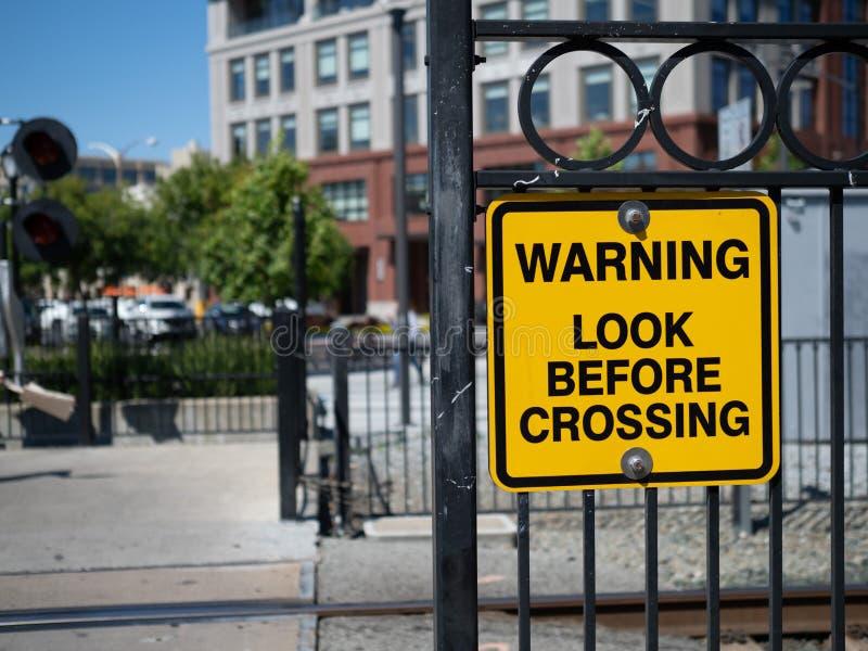 Varnande blick, innan att korsa det gula varnande tecknet på drevkorsningen i stad arkivfoto
