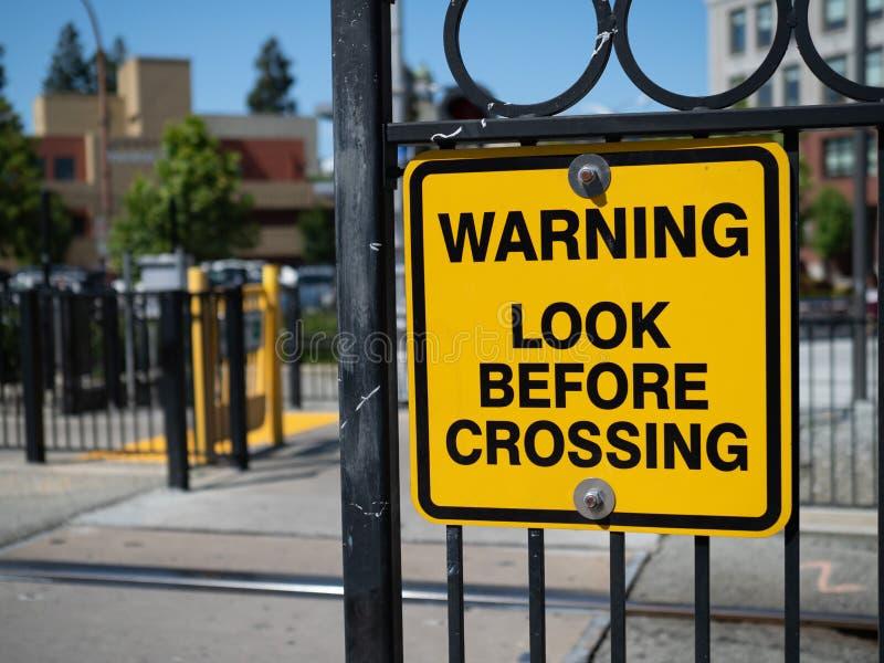Varnande blick, innan att korsa det gula varnande tecknet på drevstationen royaltyfri fotografi