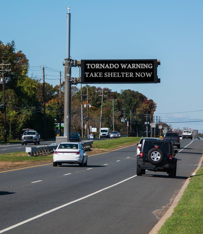 Varnande tagandeskydd för tromb nu, elektroniskt varningstecken över huvudvägen arkivfoton
