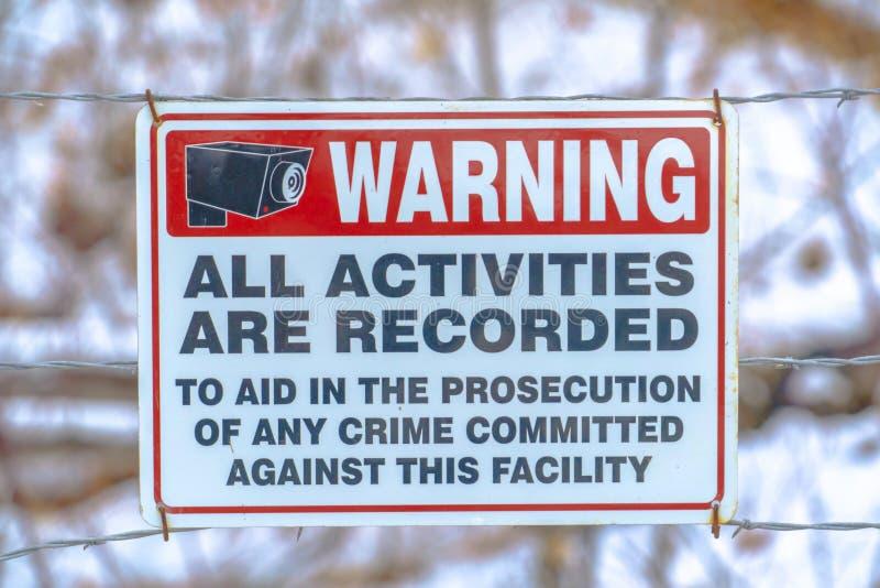 Varnande tecken på ett taggtrådstaket royaltyfri foto