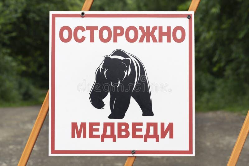 Varnande tecken på staketet i ryss: Varningsbjörnar, pictogramKamchatka brunbjörn arkivbilder
