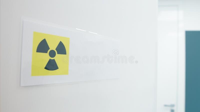 VARNING: RÖNTGA varningstecknet som I BRUK postas på öppen dörr till tand- rum arkivfoto