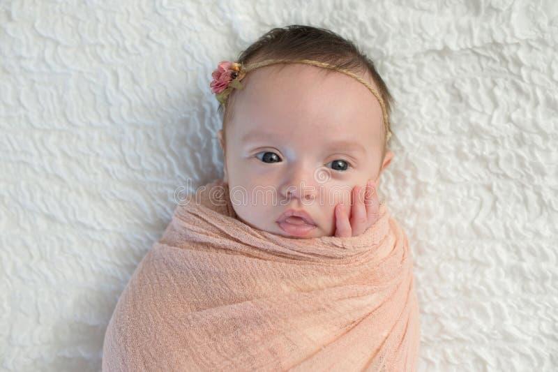 Varningen behandla som ett barn flickan som lindas i en ljus persikasjal royaltyfri fotografi