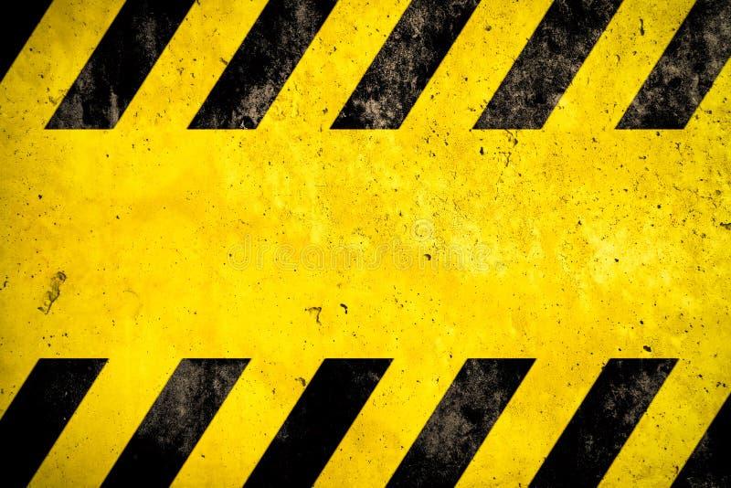 Varningsbakgrund med guling- och svartband som målas över gul betongväggfasadtextur och, tömmer utrymme för textmeddelande arkivbilder