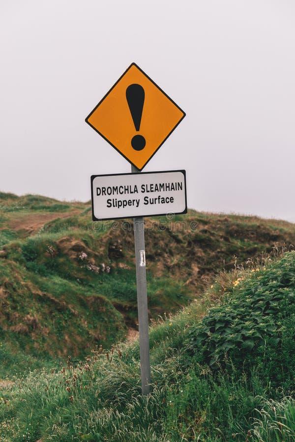 Varningstecken av hal yttersida och oskyddade kanter på den iconic omgivningen för Dunquin hamnpir i ståndsmässiga Kerry royaltyfria foton