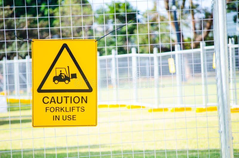 Varningstecken för i bruk för gaffeltruckar som fästas till stålstaketet arkivfoton