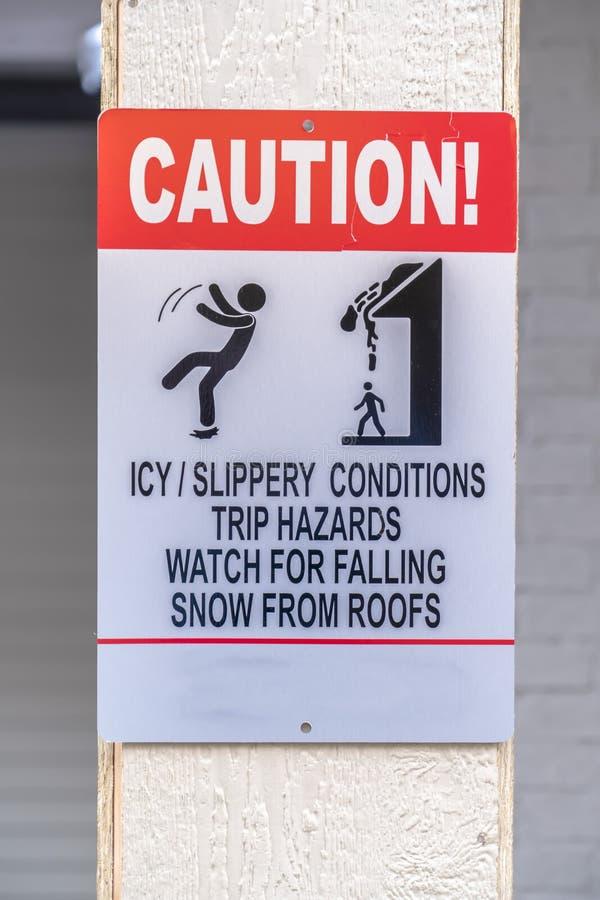 Varningstecken på halt och snöig område i vinter royaltyfri bild