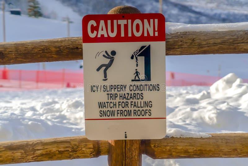 Varningstecken på trästaketet mot snö arkivbild