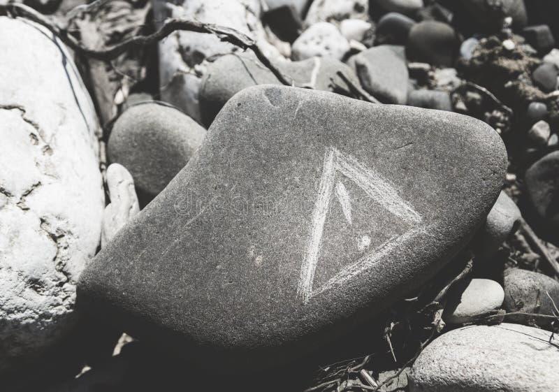 Varningstecken som skrapas på en sten royaltyfria bilder