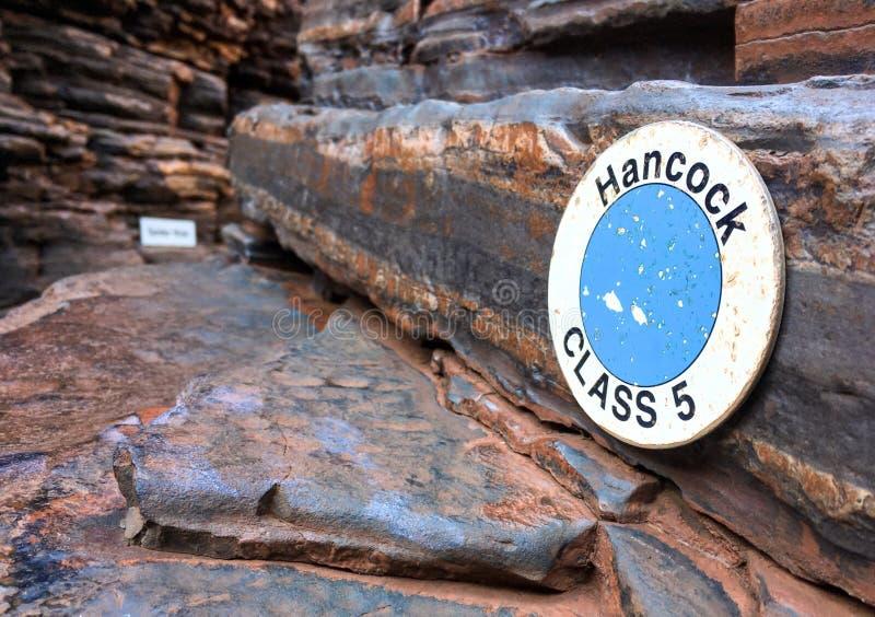 Varningstecknet i den Hancock klyftan i den Karijini nationalparken i den Pilbara regionen, västra Australien som visar svårighet royaltyfri bild